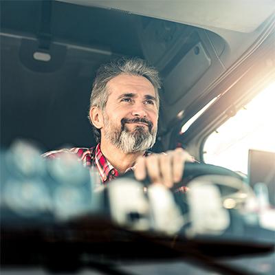 man driving behind a steering wheel
