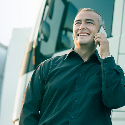 man listening to the phone besides a truck