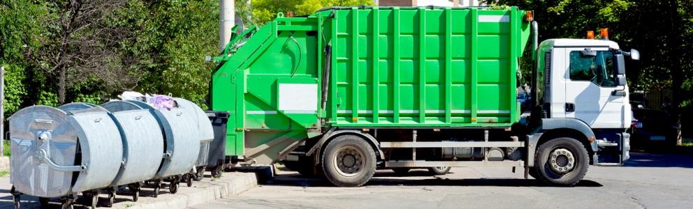 Zijaanzicht van geparkeerde groene afvalwagen