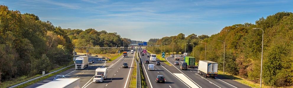 Bovenaanzicht van verkeer op Nederlandse weg in bosrijk gebied
