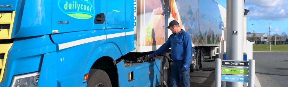 Zijaanzicht blauwe vrachtwagen Dailycool en man die de vrachtwagen voltankt